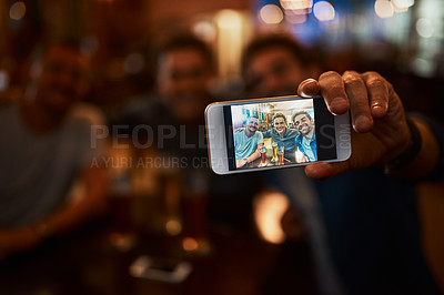 Buy stock photo Closeup of a group of cheerful young friends taking a self portrait together while enjoying beer together at a bar during the night