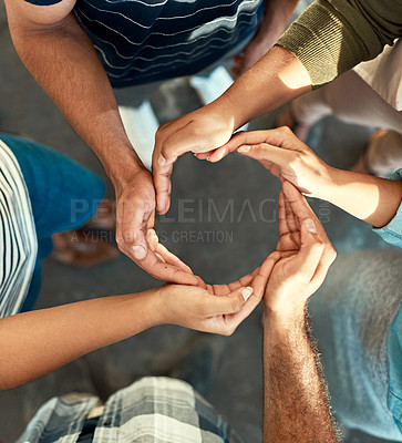 Buy stock photo High angle shot of a young group of work colleagues forming an unique huddle with their arms and hands while standing in the office at work