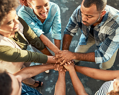 Buy stock photo Shot of a group of motivated young work colleagues forming a huddle with their hands while standing in the office at work