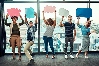 Buy stock photo Portrait of a cheerful young group of work colleagues standing next to each other while holding up signs inside of the office during the day
