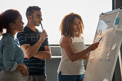 Buy stock photo Shot of a group of young designers brainstorming on a whiteboard in an office