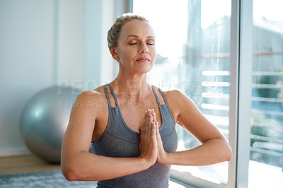 Buy stock photo Cropped shot of an attractive mature woman meditating at home