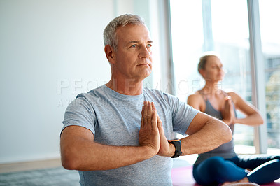 Buy stock photo Cropped shot of a handsome mature man meditating at home with his wife in the background