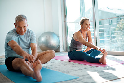 Buy stock photo Full length shot of a mature couple stretching on yoga mats before working out at home