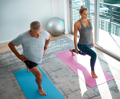 Buy stock photo High angle shot of a mature couple stretching on yoga mats before working out at home