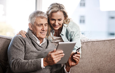 Buy stock photo Shot of a mature couple using a digital tablet and credit card to do online shopping at home