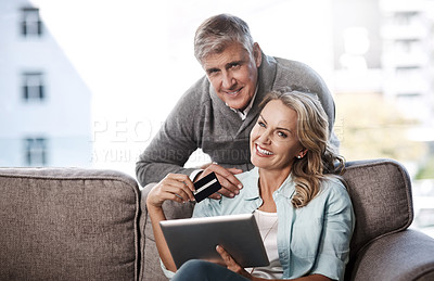 Buy stock photo Portrait of a mature couple using a digital tablet and credit card to do online shopping at home