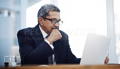 Buy stock photo Shot of a mature businessman working on a laptop in an office