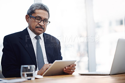 Buy stock photo Shot of a mature businessman working on a digital tablet in an office