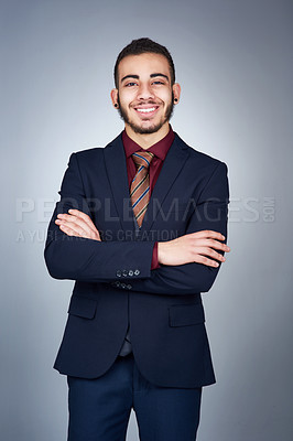 Buy stock photo Studio shot of a handsome young businessman posing against a grey background