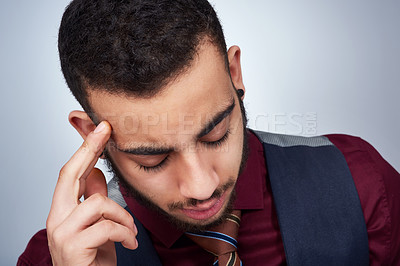 Buy stock photo Studio shot of a handsome young businessman experiencing a headache against a grey background