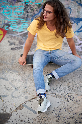 Buy stock photo Shot of a handsome young man at a skatepark outside