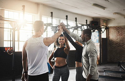 Buy stock photo Shot of a group of young people giving each other a high five during their workout in a gym