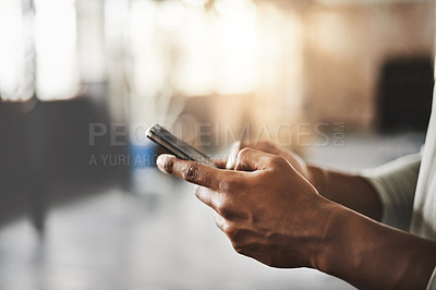 Buy stock photo Shot of an unrecognizable man using a mobile phone in a gym
