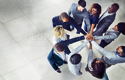 Buy stock photo High angle shot of a group of businesspeople joining hands together in solidarity in a modern office