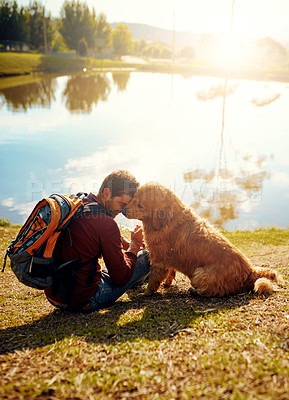 Buy stock photo Full length shot of a handsome young man and his dog sitting by a lake in the park