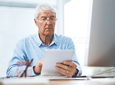 Buy stock photo Cropped shot of a handsome senior businessman working on a tablet at home