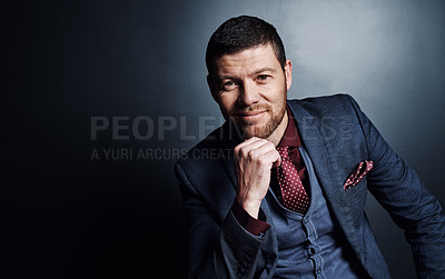 Buy stock photo Cropped portrait of a handsome young businessman sitting with his hand on his chin against a dark background