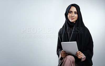 Buy stock photo Cropped portrait of an attractive young businesswoman using her tablet while sitting against a grey background