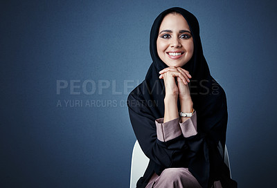 Buy stock photo Cropped portrait of an attractive young businesswoman sitting in the studio against a dark background