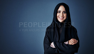 Buy stock photo Cropped portrait of an attractive young businesswoman standing with her arms folded against a dark background