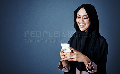 Buy stock photo Cropped shot of an attractive young businesswoman sending a text while standing against a dark background