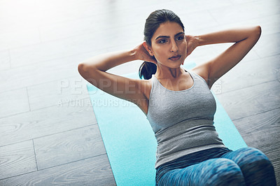 Buy stock photo Shot of an attractive young woman doing sit ups in a gym