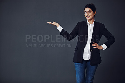 Buy stock photo Studio shot of an attractive young businesswoman pointing at copy space against a dark background