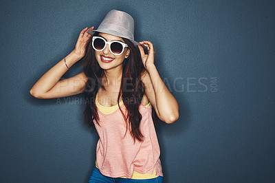 Buy stock photo Studio shot of an attractive and fun loving young woman posing against a dark background