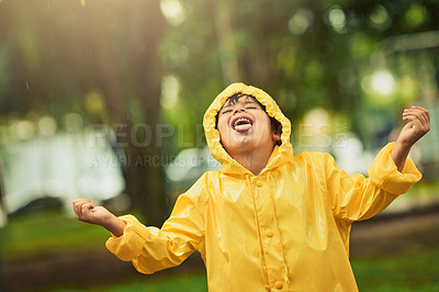 Buy stock photo Cropped shot of an adorable little boy in the rain outside