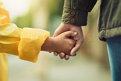Buy stock photo Closeup shot of an unrecognizable little boy and his mother holding hands in the rain outside