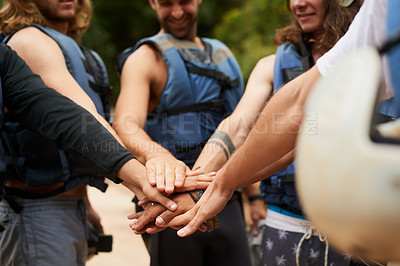 Buy stock photo Cropped shot of a group of young male friends joining hands in unity before going white water rafting