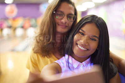 Buy stock photo Cropped shot of a beautiful young couple taking a selfie while on a date in a bowling alley