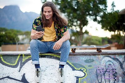 Buy stock photo Shot of a handsome young man using a cellphone at a skatepark outside