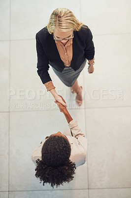 Buy stock photo High angle shot of two confident young businesswomen shaking hands in agreement while standing in the office during the day