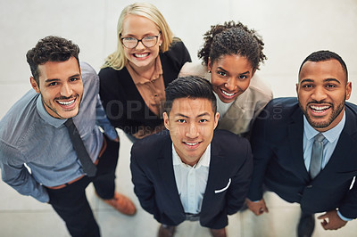Buy stock photo High angle portrait of a group of cheerful young businesspeople  standing together in the office during the day