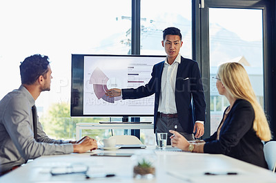 Buy stock photo Shot of a young businessman delivering a presentation to his colleagues in the boardroom of a modern office