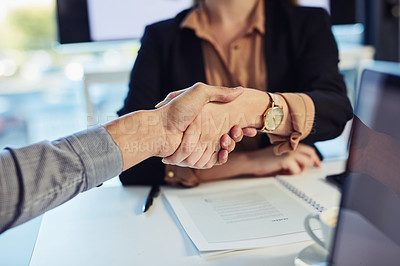 Buy stock photo Cropped shot of a businesswoman and businessman shaking hands during a meeting in a modern office