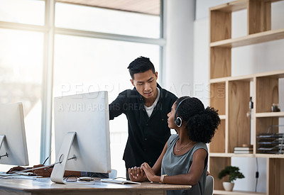 Buy stock photo Shot of a young businessman assisting his colleague in a call centre