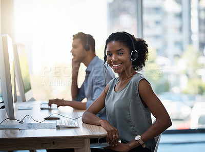 Buy stock photo Portrait of a young call centre agent working alongside her colleague in an office