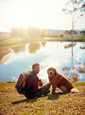 Buy stock photo Full length portrait of a handsome young man and his dog sitting by a lake in the park