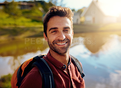 Buy stock photo Cropped portrait of a handsome young man spending the day at a lake