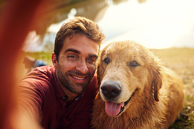 Buy stock photo Cropped shot of a handsome young man and his dog taking selfies by a lake in the park