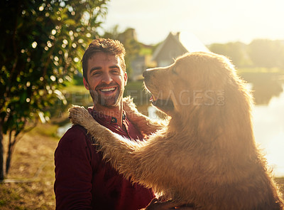 Buy stock photo Cropped portrait of a handsome young man and his dog spending the day by a lake in the park