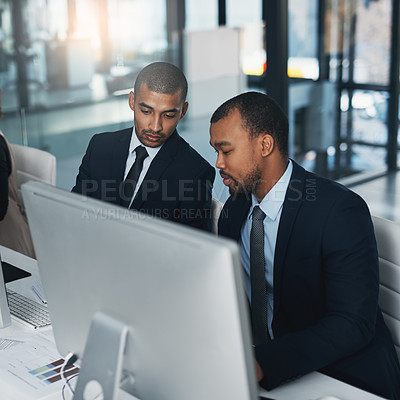 Buy stock photo High angle shot of two corporate businessmen working together on a computer in the office