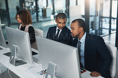 Buy stock photo High angle shot of three corporate businesspeople working on their computers in the office