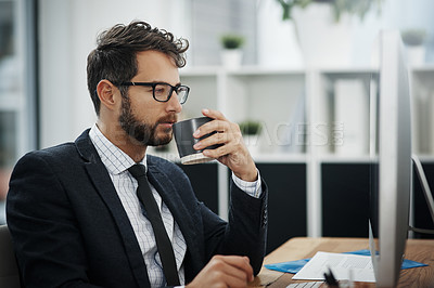 Buy stock photo Shot of a young businessman drinking coffee while working in an office
