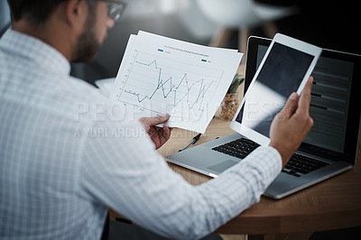 Buy stock photo Shot of a young businessman using a digital tablet while analyzing graphs in an office
