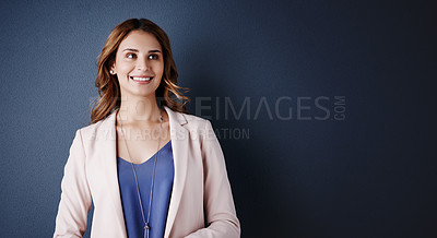 Buy stock photo Studio shot of an attractive young businesswoman looking thoughtful against a dark blue background