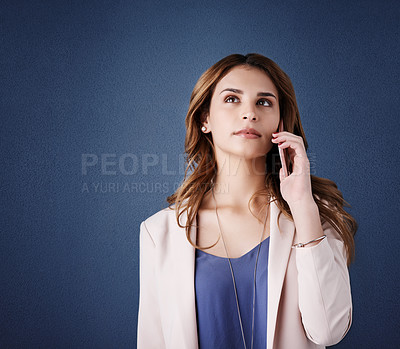 Buy stock photo Studio shot of an attractive young businesswoman using a mobile phone against a dark blue background